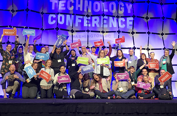 Group photo of NTEN's community organizers on a stage at the 17NTC. They are holding us signs that designate what city they're from or what online group they represent. They are laughing and having a good time.