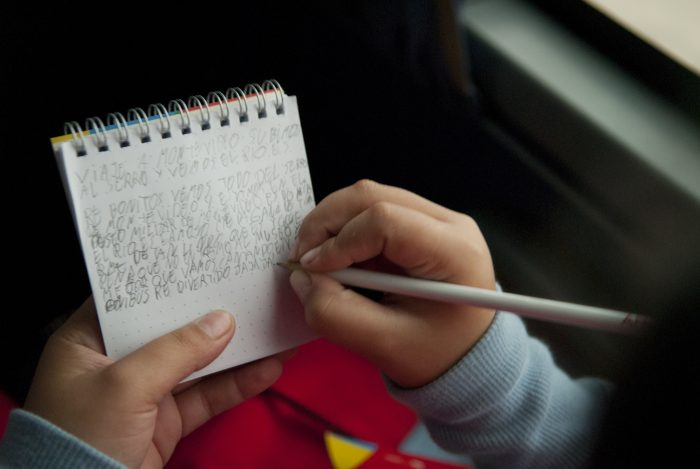 Person writing with small tablet and pencil.