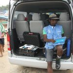 UNICEF staffperson using laptop in back of open van