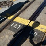 "Two shadows on train tracks with ""Let Go"" caption"
