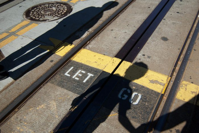 Two shadows on train tracks with Let Go caption