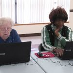 Digital Inclusion at work: Two senior women sit at tables in front of laptops.