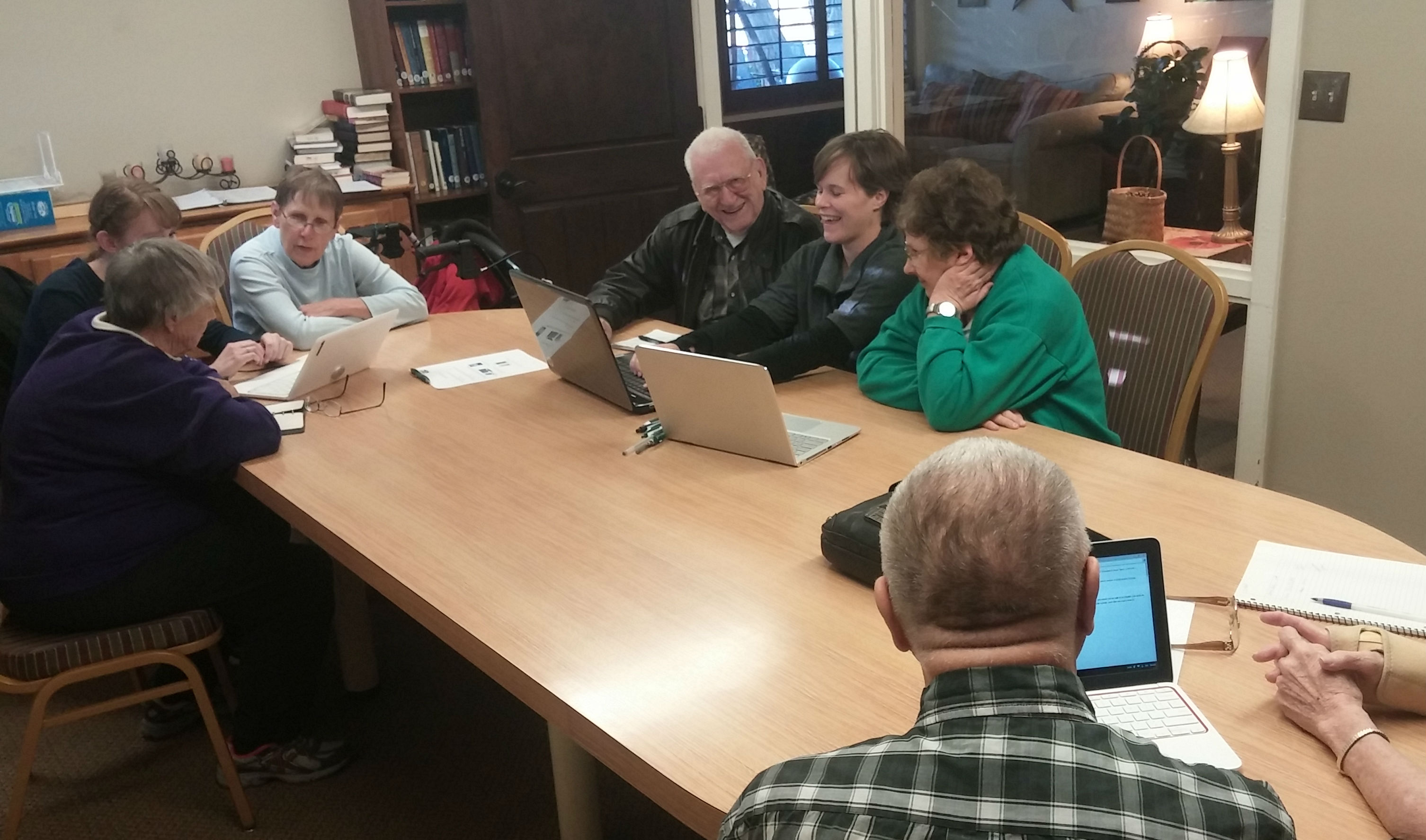 Elders gather around a laptop, smiling.