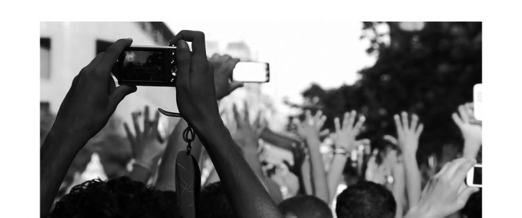 B&W photo of hands in the air, some recording video with their cell phones