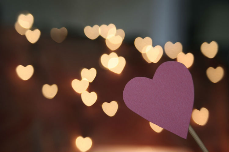 photo of a pink heart on a stick, in focus, with heart-shaped lights in the dark background, slightly blurry
