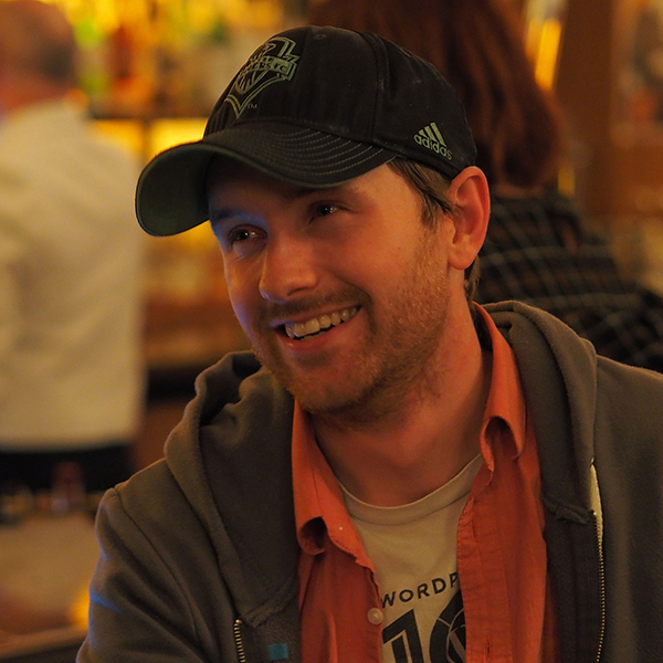 Close-up of Mark Root-Wiley, wearing a dark baseball cap and smiling