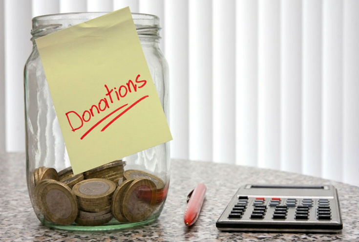 photo of a glass jar partially filled with coins with a pale yellow sticky note attached to the front with the word Donations written on it; next to the jar is a red pen and a calculator