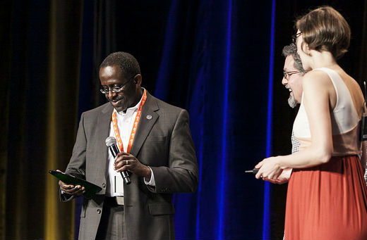 photo of Leon Wilson onstage, looking down at the award in his hand, while 2 people, also onstage, look on