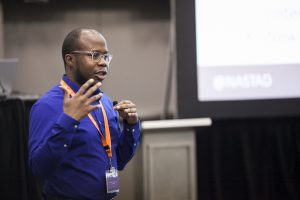 A speaker at the 2016 Nonprofit Technology Conference, wearing a vivid deep purple shirt and gesturing with his hands