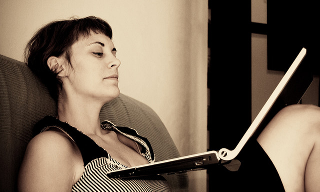 Sepia-toned photo of a pale-skinned woman with short dark hair sitting on a couch with her knees up, looking at a laptop which is resting on her chest and thighs