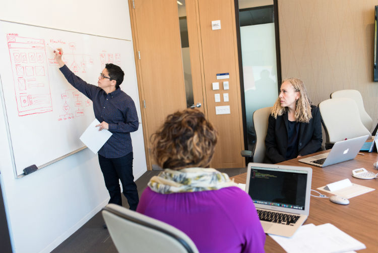 3 people meeting: 1 person drawing a diagram on a white board and 2 people seated at a table, one with an open laptop in front of her.