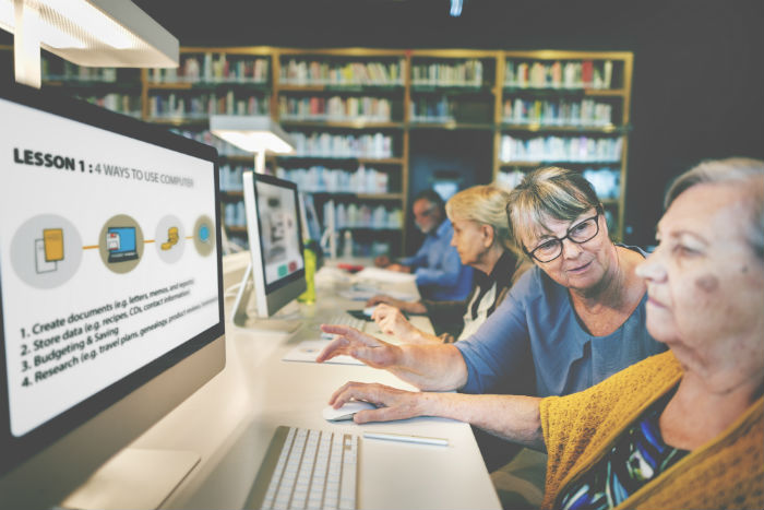 Photo of two older women in front of a computer in a public library