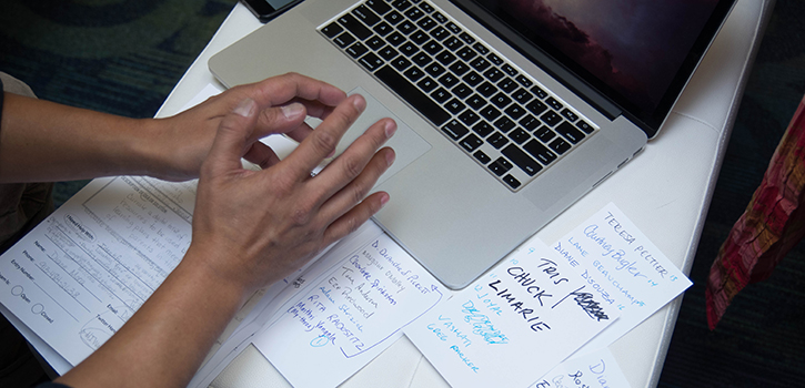 nonprofit technology worker hands with laptop and papers
