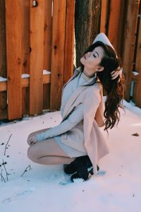 young woman with long dark hair posing in a crouched position outdoors. there is a wood fence behind her and light snow on the ground