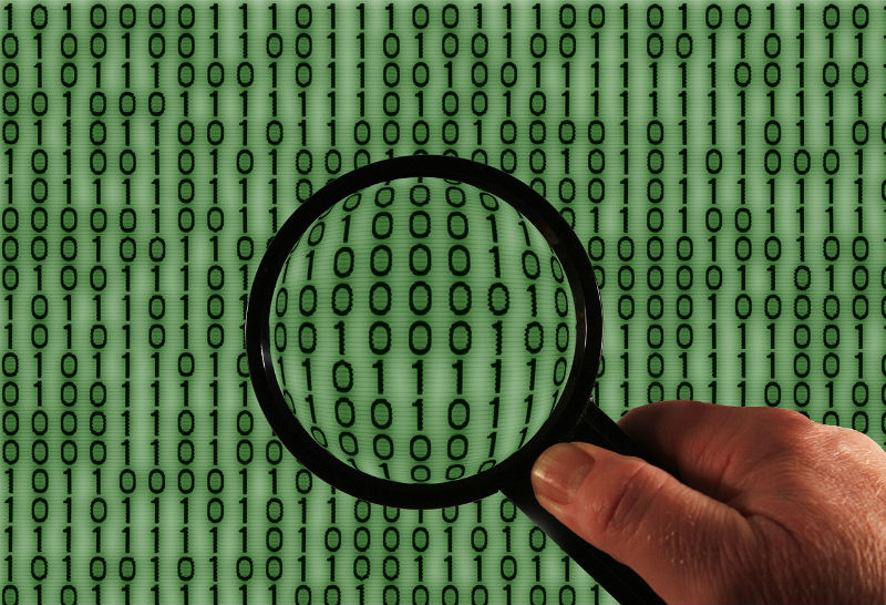 a black magnifying glass being held over a pale green background of binary numbers in black