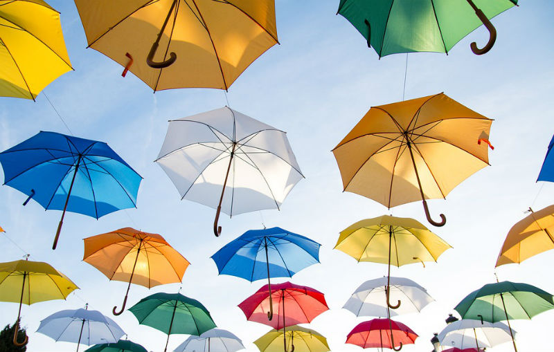umbrellas in various colors hanging against a pale blue sky