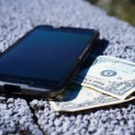 Photo of dollar bills under a mobile phone, on a concrete surface