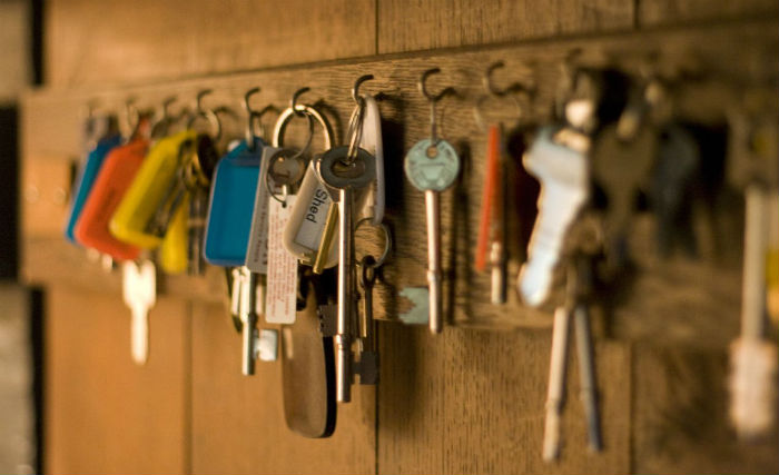 Close-up photo of many sets of keys hanging from hooks in a wooden wall.