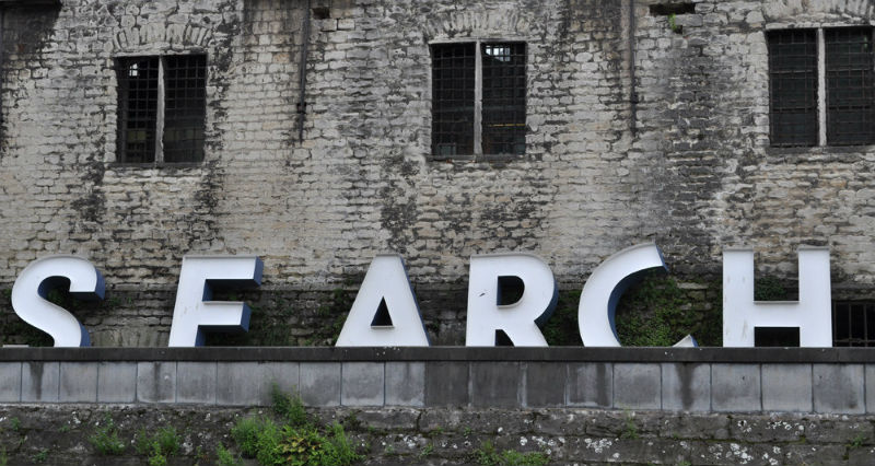 "Photo of large letters leaning against a weathered brick wall, spelling out ""SEARCH"""
