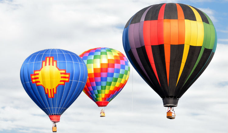 3 colorful hot air balloons in the sky, one featuring the New Mexico state flag