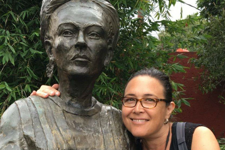 A photo of Pattie Carlin posing with a statue of artist Frida Kahlo.
