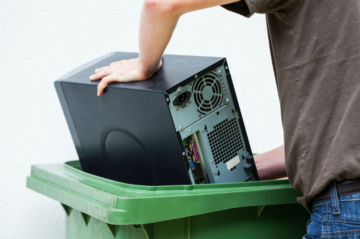 close-up of a man stuffing an old CPU into a recycling bin