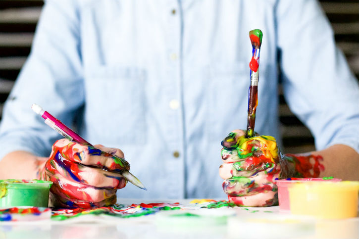 close-up on hands of someone painting, with multiple colors of paint all over his hands and the table and paintbrushes in one hand
