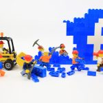 "Lego-figurine construction people work on a blue Lego structure with the Facebook ""f"" built in"