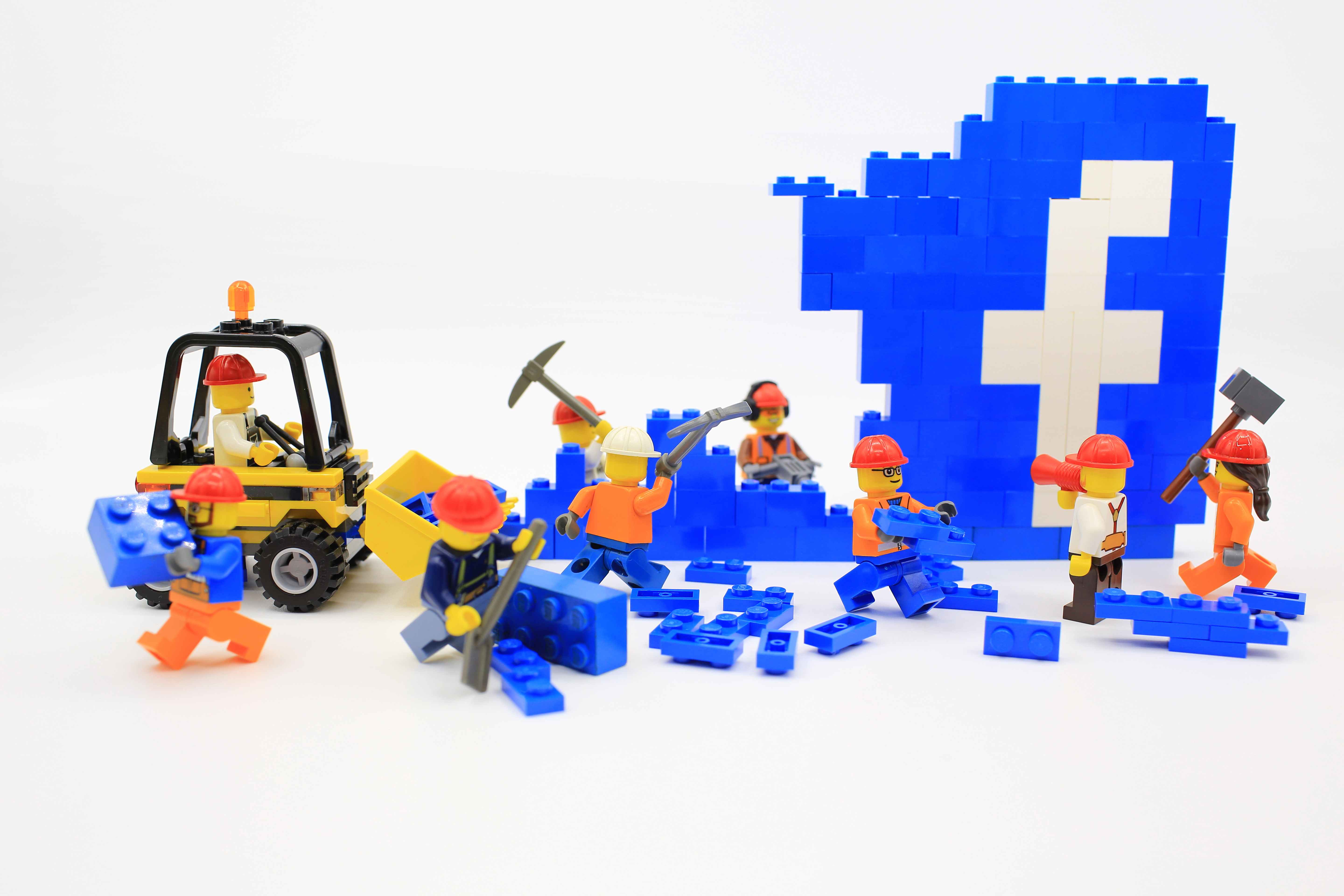 Lego-figurine construction people work on a blue Lego structure with the Facebook f built in