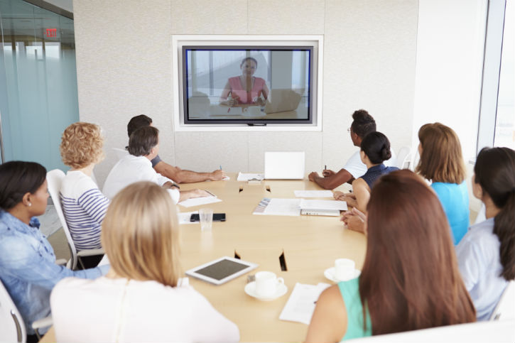 several people gathered around a conference table, looking at a large screen on the wall where another person is video conferencing