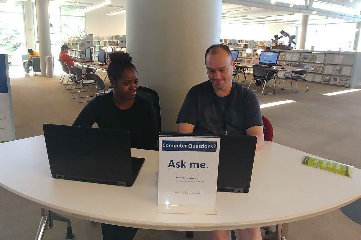 "Photo of 2 people sitting at a rounded desk, with their open laptops in front of them. A sign on the desk reads ""Computer questions? Ask me."""