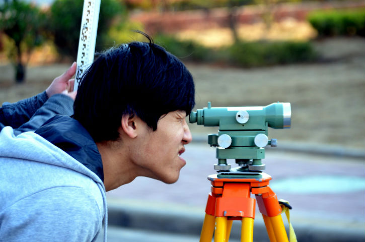 A man of Asian descent peers through a surveying tool