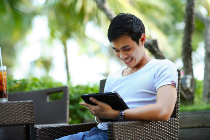 person outside, looking at tablet and smiling