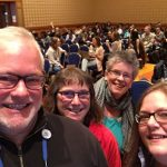 selfie-style photo of 4 smiling people at a conference