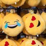 Emoji plush toys hang on a rack: Crying, heart eyes, hungry
