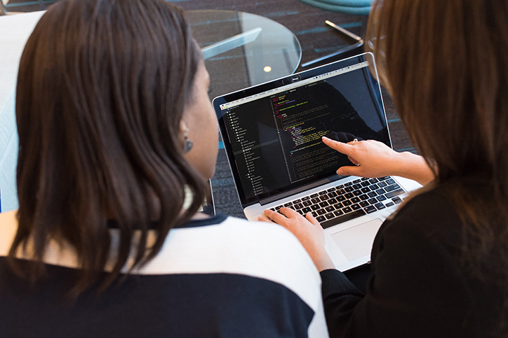 Two women looking at computer code