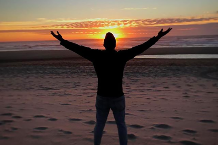Man standing with open arms at the beach