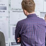 Three people looking at a project workflow board