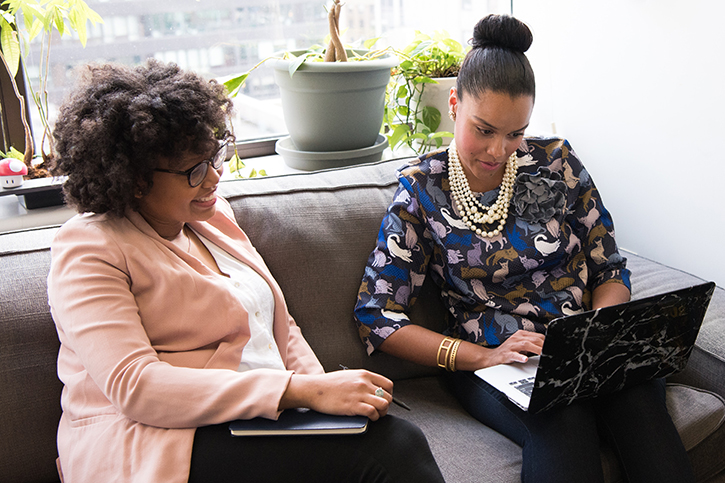 Two women with laptops sitting together