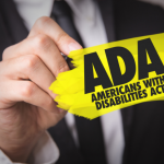 "Hand scribbling yellow ink on glass to make ""ADA Americans With Disabilities"" visible"