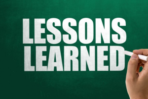 A hand writing LESSONS LEARNED on a chalkboard.