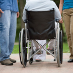 Several people standing outside with a person using a wheelchair
