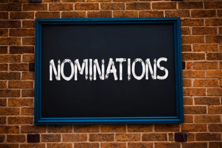 NOMINATIONS written on a chalkboard hanging on a brick wall
