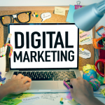 """Hands are typing on a laptop. The screen reads, """"DIGITAL MARKETING."""""""
