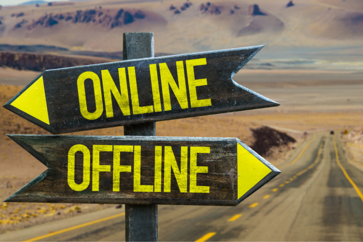 A closeup of a road sign with two arrows pointing in opposite directions. One is labeled, Online, and the other is labeled, OFFLINE.
