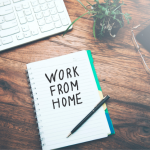 """An open spiral-bound pad with, """"WORK FROM HOME"""" on the page. Around it is a keyboard, a plant, glasses, and a cup of coffee."""
