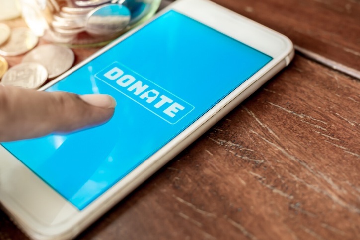 DONATE appears in white on a blue phone screen. An index finger hovers above the phone.