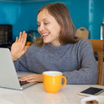 A woman sits in her kitchen and waves to her laptop camera