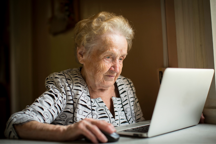 An older woman uses a mouse and a laptop