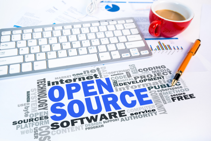 OPEN SOURCE in blue, surrounded by words like software, community, internet, and technology. A keyboard, pen, and coffee mug frame the word cloud.